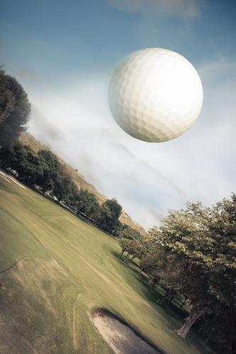 Golf ball flying over green field
